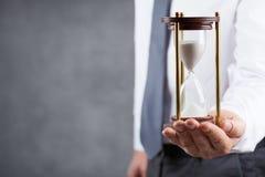 商人在他的手上的拿着滴漏 最后期限和时间安排概念 免版税库存照片