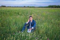 商人在他的衣服坐给f打电话的一个绿色晴朗的领域 库存照片