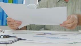 商人在会计办公室浏览和读的文件页 股票录像