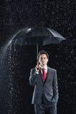 年轻商人在伞下在雨中 库存图片