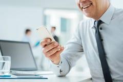 商人在使用一个巧妙的电话的办公室 免版税图库摄影