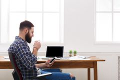 商人在使用手机的办公室由膝上型计算机 免版税库存照片