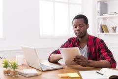 黑商人在偶然办公室,工作两个在膝上型计算机和片剂 免版税图库摄影