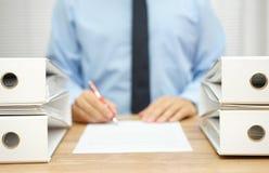 商人在公司中写着关于不规则性的报告 免版税库存图片
