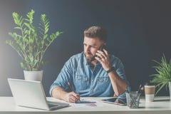 商人在办公室在手机坐在桌上并且谈话,当看膝上型计算机屏幕和做笔记时 免版税库存图片