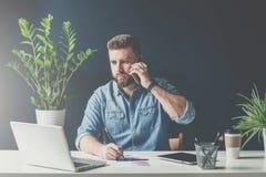 商人在办公室在手机坐在桌上并且谈话,当看膝上型计算机屏幕和做笔记时 库存图片