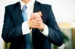 商人在办公室用他的被折叠的手 免版税库存图片