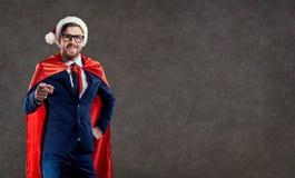 商人在圣诞老人服装超级英雄指向与他的飞翅 库存图片