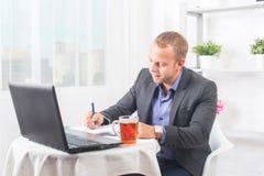 商人在坐在与膝上型计算机的桌上的办公室写集中 免版税库存照片