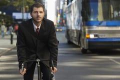 商人在城市街道上的骑马自行车 库存图片