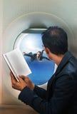商人在客机位子和看的阅读书 库存照片