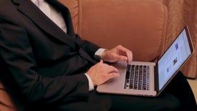 商人在家浏览互联网长沙发的 股票录像