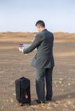 商人在带着手提箱的一片沙漠,看地图 库存图片