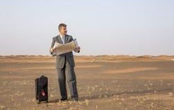 商人在带着手提箱的一片沙漠,看地图 免版税库存图片