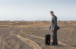 商人在带着手提箱的一片沙漠 免版税库存照片