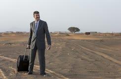 商人在带着手提箱的一片沙漠 库存照片
