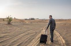 商人在带着手提箱的一片沙漠 库存图片