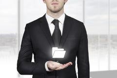 商人在开放手上的举行文件夹标志 图库摄影