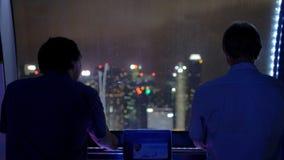 商人在弗累斯大转轮站立在大厦的夜神色在新加坡市背景中  免版税库存照片
