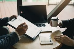 商人在战略讨论时指出了在桌上的公司性能图表并且喝了咖啡早晨  库存图片