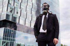 商人在戴着在面孔的城市一个防毒面具 免版税库存图片