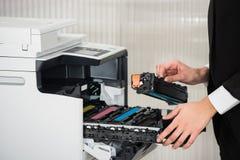 商人在打印机机器的定象弹药筒在办公室 免版税库存照片