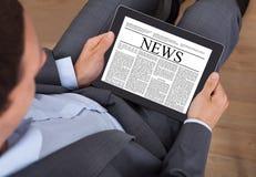 商人在数字式片剂的读书新闻在办公室 免版税库存照片