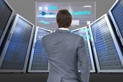 商人在数据中心的观看一个数字式屏幕 免版税库存照片
