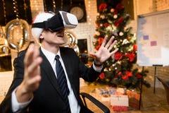 商人在新年`的s伊芙办公室 他头戴一件虚拟现实盔甲的` s和他打比赛的` s 库存照片