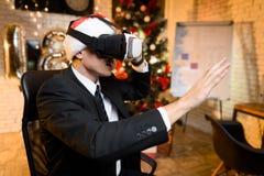商人在新年`的s伊芙办公室 他头戴一件虚拟现实盔甲的` s和他打比赛的` s 免版税库存图片