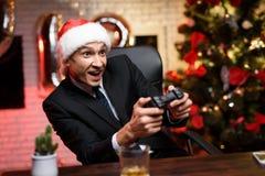 商人在新年`的s伊芙办公室 他是热情关于比赛控制台并且有gamepad在他的手上 免版税库存照片