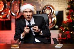 商人在新年`的s伊芙办公室 他是热情关于比赛控制台并且有gamepad在他的手上 库存图片