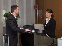 商人在旅馆和登记到达 免版税库存照片