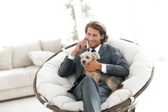 商人在智能手机拿着他的宠物并且谈话,当坐在一把舒适的椅子时 库存照片