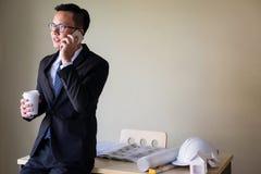 商人在智能手机的工程师谈话 库存照片