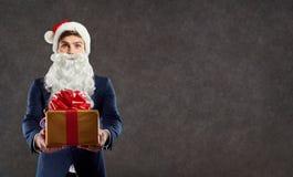 商人在有一件礼物的圣诞老人服装在他的手上 免版税库存照片