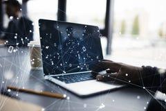 商人在有一台膝上型计算机的办公室工作有互联网作用的 互联网分享和公司起动的概念 免版税库存图片