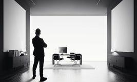 商人在有两空的帆布的现代办公室站立 黑色白色 免版税库存照片
