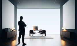 商人在有两空的帆布的现代办公室站立 颜色 免版税库存照片
