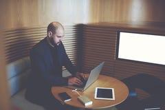 商人在有嘲笑的办公室内部近的屏幕坐拷贝空间 免版税图库摄影