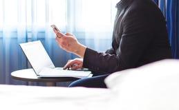商人在有智能手机和膝上型计算机的旅馆客房 免版税库存照片