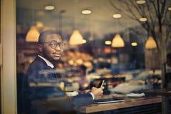 商人在有智能手机的一家餐馆 库存图片