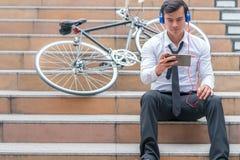 商人在机动性的手表录影与他的在边的自行车 图库摄影