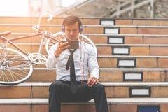商人在机动性的手表录影与他的在边的自行车 库存照片