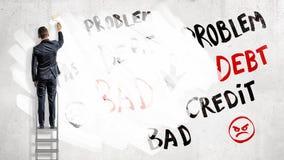 商人在梯凳和油漆站立在词问题、债务和信用与一个白色漆滚筒 免版税库存照片