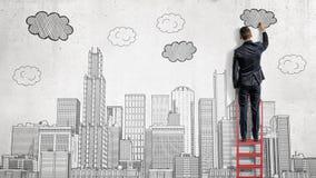 商人在梯子站立并且画有云彩的一个大城市在摩天大楼上 免版税库存照片