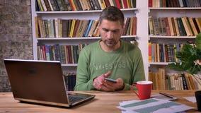 商人在浏览的膝上型计算机和的传讯前面坐电话 在背景的书架 股票录像