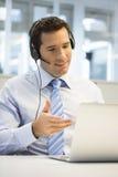 商人在电话的办公室有耳机的, Skype 免版税库存照片