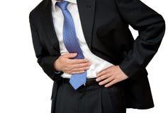 商人在痛苦中的握他的胃与stomachache或消化不良 免版税库存图片