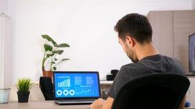 商人在看在有生气蓬勃的数据的屏幕上的便衣在家绘制分析图表 股票视频